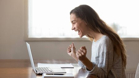 Overjoyed millennial girl sit at table at home look at laptop screen feel euphoric winning online lottery or game, excited young woman triumph reading amazing good news get approval on computer Stock fotó