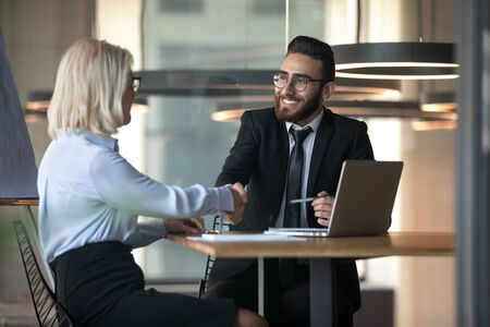 Middle eastern ethnicity HR manager hiring elderly woman satisfied diverse people shake hands finish job interview or client and company representative greeting each other starting negotiation concept Standard-Bild