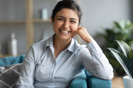 Profile picture of smiling beautiful millennial Indian girl sit rest on couch in living room, portrait of happy young ethnic woman relax on comfortable sofa at home look at camera feel positive