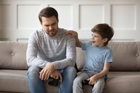 Happy small child boy put hand on fathers shoulder, supporting after losing video game. Excited little son feeling joyful after winning game, having fun together in living room.