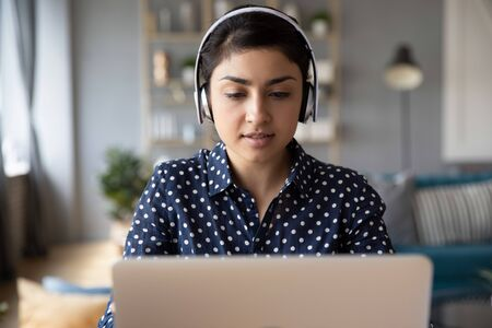 Concentrated millennial Indian girl in wireless earphones study online take Internet educational course on laptop at home, focused young ethnic female work on modern computer, browse web or shopping