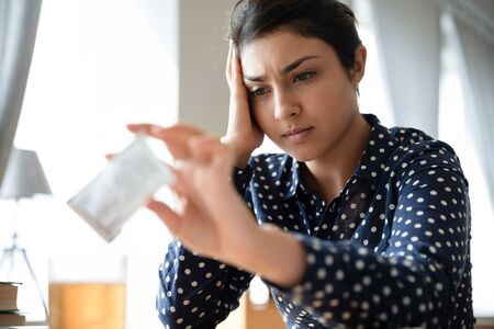 Sick Indian girl pour dissolving powder from sachet into glass relieve fever or flu symptoms, unhealthy ill ethnic woman drink hot tea, take medication from high temperature, healthcare concept