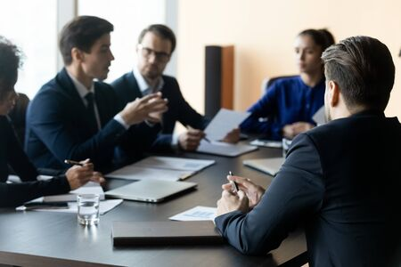 Close up businessman back sit at table in boardroom at company meeting. Confident employee listens business mentor telling about business strategy with colleagues at briefing.