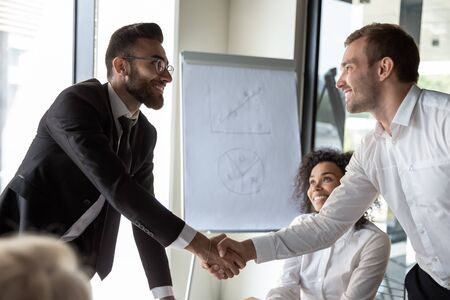 Arabian and Caucasian ethnicity businesspeople shake hands after signing contract accomplish successful negotiations, executive manager handshake client satisfied with effective group meeting concept
