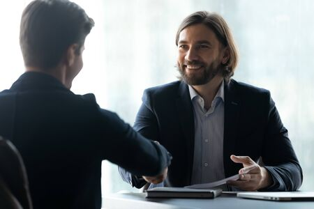 Smiling businessman in suit shaking hands with job seeker. Happy successful male manager making deal with partner. Professional employee secured contract with gesture.