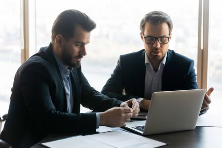Serious businessman coaching partner looking at laptop screen. Male manager discuss business moments with leader in office at workplace. Boss listening and watching presentation at meeting.