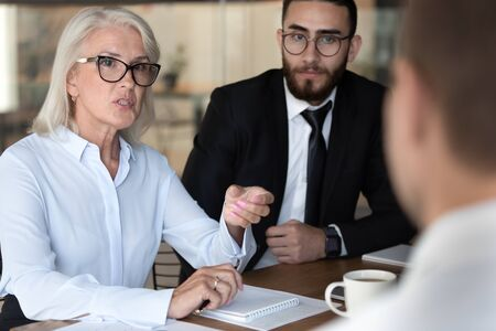 Negotiations lead by middle-aged boss talking with client diverse business people gathered together at boardroom, job interview process european and arabian HR managers interweaving applicant concept