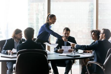 Happy executive businesswoman manager gives handout in boardroom at meeting. Smiling female teacher coach lead new project presentation for colleagues, conversation at negotiation, discussing results