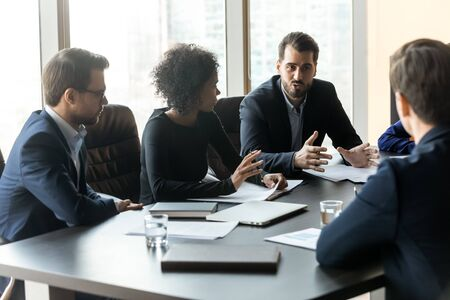Serious businessman telling diverse employees about project sit at table in boardroom at company meeting. Confident leader discuss business strategy with african american woman and colleagues. Banque d'images