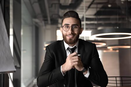 Young middle eastern ethnicity businessman looking at camera make video call having distant online conversation with partners, business coach mentor recording webinar or distance job interview concept