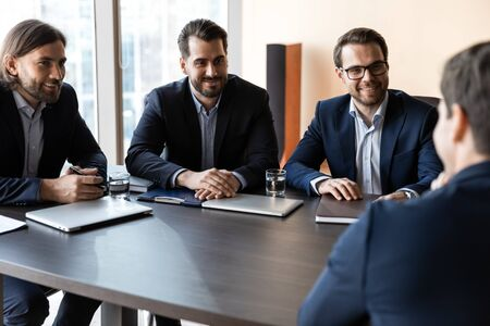 Applicant sitting in front three happy HR businessmen speaking during work interview in office. Young job seeker presenting herself to smiling managers in suit. Candidate at job meeting concept.