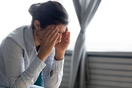Upset young Indian woman feel stressed depressed crying suffering from life relationship problems, sad millennial ethnic girl struggle with headache or migraine, have depression or mental trouble
