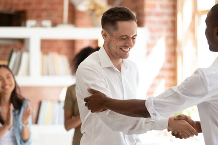 Smiling employee getting promoted, handshaking with African American boss, team leader congratulating subordinate, thanking for good work result, shaking hand of subordinate, showing respect