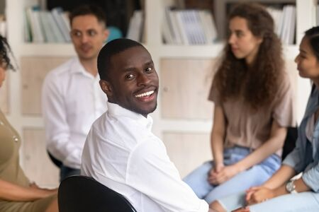 Head shot portrait of smiling African American man sitting at group therapy session, male psychologist looking at camera, coach counselor psychotherapist posing for photo with diverse people Foto de archivo