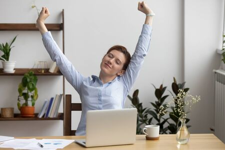 Satisfied businesswoman stretching at workplace after finished work, sitting in comfortable chair, happy employee with closed eyes relaxing during break, breathing deep, feeling no stress