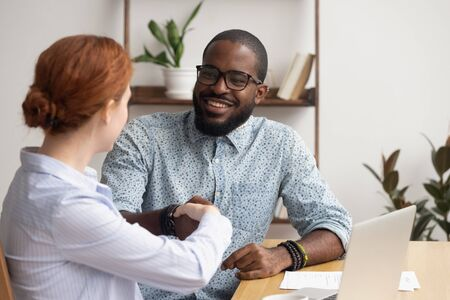 Businesswoman shaking hand of smiling African American colleague at workplace, get acquainted, team start working together, mentor greeting trainee, manager handshaking with client, successful deal Stockfoto