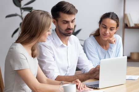 Confident businessman, mentor helping female trainees with new software, staff training concept, colleagues working on online project together in office, employees using laptop, looking at screen Archivio Fotografico