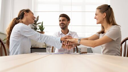 Excited colleagues joining hands, celebrating business success, achievement at meeting, employees team motivated for better teamwork result, team building activity in office at briefing Stock Photo