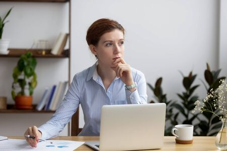 Pensive businesswoman thinking about project, working on financial report, using laptop, sitting at desk, thoughtful female employee pondering business strategy, solving problem, planning
