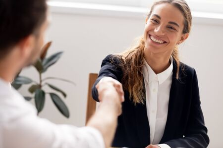 Smiling candidate shaking hand of hr manager, successful interview, business partners greeting each other, get job, satisfied client making insurance agreement or taking loan close up Standard-Bild