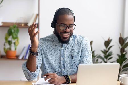 Lächelnder afroamerikanischer Mitarbeiter in Kopfhörern mit Laptop, Blick auf den Bildschirm, Videoanruf oder Webinar, Notizen schreiben, Sprachkonzept für Fernunterricht, Call-Center-Betreiber arbeiten