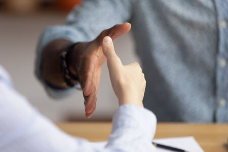 Close up African American businessman shaking hand of candidate at job interview, hiring process, greeting business partner at meeting, making agreement, signing contract, partnership concept