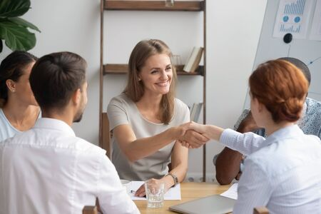 Smiling businesswoman shaking hand of business partner at meeting, greeting, making agreement, team leader, boss congratulating subordinate with promotion, thanking for good work results