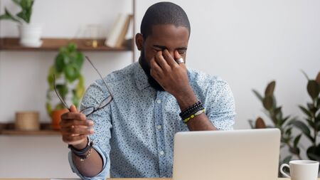Tired African American businessman taking off glasses, exhausted employee massaging nose bridge, suffering from eye strain after long computer work, feeling pain, health problem concept