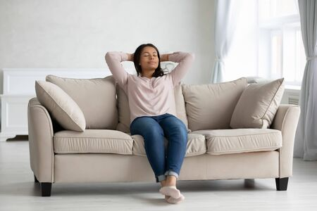Calm African American woman sit rest on comfortable couch in living room take nap daydream, tired biracial young female relax sleep on cozy sofa at home, breathe fresh air, stress free concept