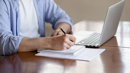 Close up of concentrated male student busy studying using laptop make notes in notebook, focused man worker employee write watching webinar or online training course on computer, education concept