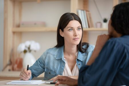 Head shot attentive young female company employee listening to african american client in office, writing down notes. Pleasant skilled hr manager holding job interview with mixed race applicant. Foto de archivo