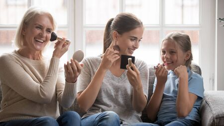 Happy three generations millennial woman with smiling middle aged mother and school age daughter doing make up together, sitting on sofa, having fun, preparing for special family occasion at home. Reklamní fotografie