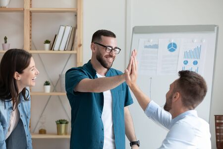 Excited male team leader in glasses giving high five to happy coworker at brainstorming meeting in office. Happy colleagues celebrating business success, good decision together in workplace.