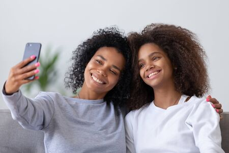 Happy family young african american mom with teen daughter take selfie on smartphone, smiling mixed race black mother and teenage girl make snapshot self portrait on phone use mobile app at home