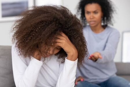 Upset african american teenage girl feeling sad turned back to angry strict black mother scolding lecturing difficult kid for bad behavior, mad mom arguing shouting at stubborn child teen daughter 写真素材