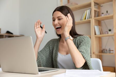 Overjoyed young businesswoman looking at laptop screen, received message with good news. Head shot happy female company employee manager professional feeling excited about project results in office. Stockfoto