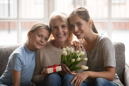Happy three generation family celebrating grandmothers birthday portrait. Smiling middle aged woman holding flower bouquet and holiday wrapped gift box, receiving congratulations with special event. Reklamní fotografie
