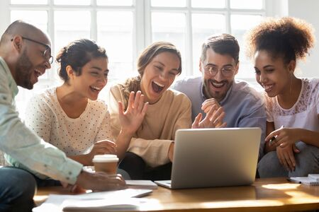Five multi-ethnic millennial friends sitting on sofa looking at computer screen wave hands laughing enjoy distant communication with mate. Make videocall, greeting online by webcam modern tech concept