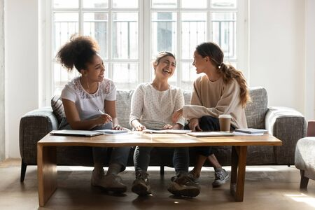 Diverse girls friends laughing sit on sofa in cozy warm room chatting take break during study process, preparation for university entrance exams college research project, friendship teamwork concept