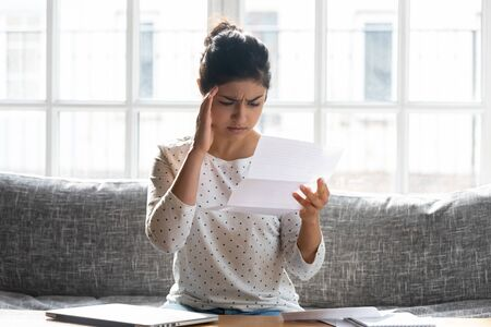 Frustrated indian ethnicity young woman sit on sofa at home holding paper letter reading bad news about company job refusal, college admission, bank loan rejection or notification about debt concept Banco de Imagens