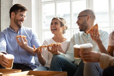 Indian ethnicity girl spend free time with best multi-ethnic friends, diverse young people gathered together indoors sit on sofa laughing telling anecdotes feels happy, enjoy coffee and ordered pizza