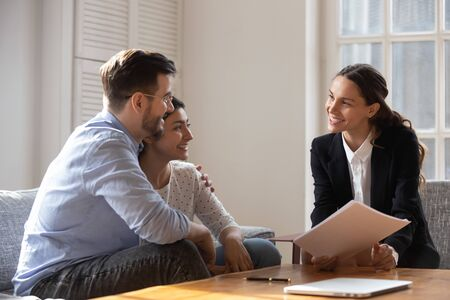Multiracial couple Indian wife Caucasian husband hugging feels satisfied with meeting results with realtor, diverse people client and banker seated on sofa discuss mortgage loan contract terms concept