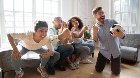 Group of multi-racial best friends gathered together indoors watching football supporting favorite soccer team waiting for goal and victory, european guy holding ball enjoy game with buddies at home