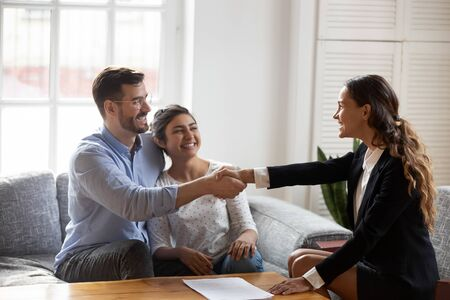 Female realtor or landlord shake hands with multiracial couple real-estate buyers make deal sign rental agreement or sale purchase contract, agent and happy clients renters, buying first home concept