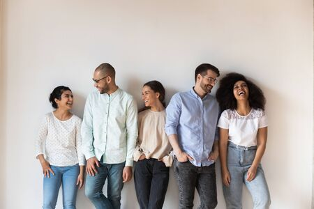 Isolated on grey beige wall five cheerful multi-ethnic friends laughing enjoy live communication together, intimates warm relations, friendship racial equality, like-minded people having fun concept Banco de Imagens