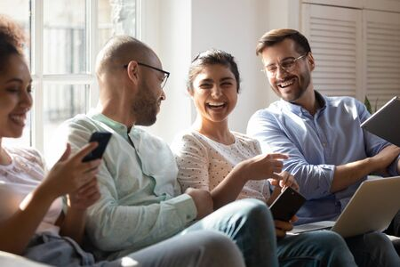 Diverse friends gathered together spend free time with modern devices sitting on sofa having fun laughing enjoy live and virtual chat, generation addicted to gadgets, friendship, communication concept Stock fotó