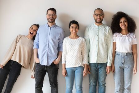 Five attractive cheerful multi-ethnic best friends, teammates, students or colleagues having fun fooling around posing looking at camera standing in row gather together for funny photo near grey wall