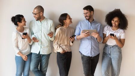 Near wall pose five diverse girls guys holding modern wireless devices enjoy social network activity virtual and live communication, generation addicted with gadgets and multiracial friendship concept