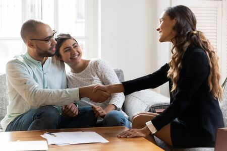 Female realtor congratulates multi-ethnic couple with signing rental agreement, client and agent shake hands. Insurance broker and customers family finish successful meeting make purchase deal concept Banco de Imagens