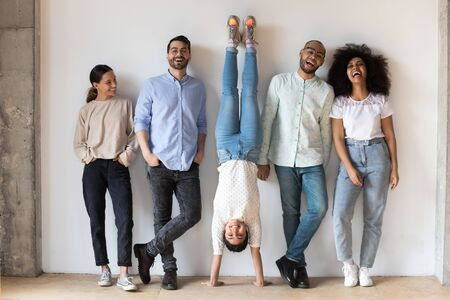 Indian girl fools around standing on hands upside-down having fun during photo shooting with multi-ethnic friends. Full length five cheery buddies laughing photographing posing near grey wall indoors Banco de Imagens